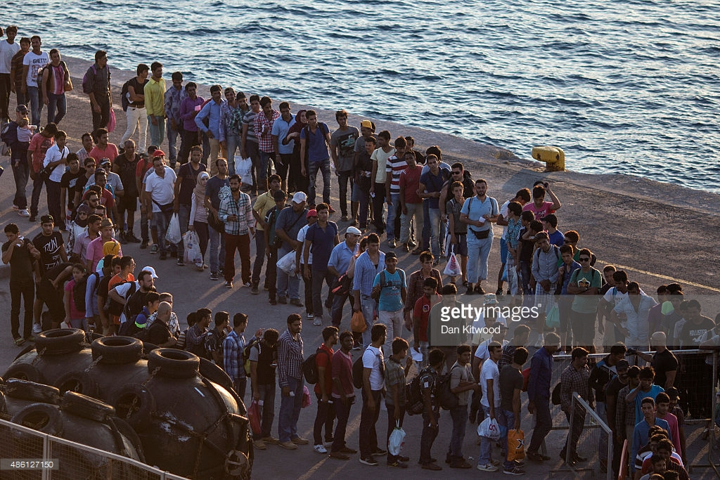 486127150-migrants-wait-to-board-a-ferry-from-the-gettyimages