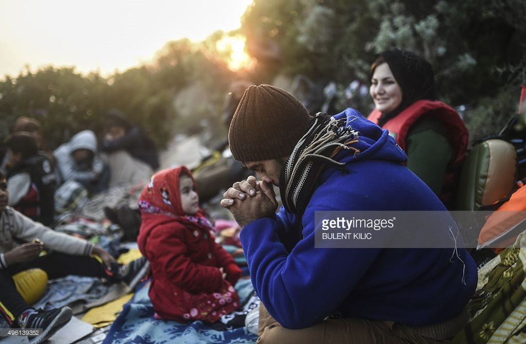 man-prays-next-to-other-migrants-and-refugees-as-they-wait-for-the-picture-id496139352
