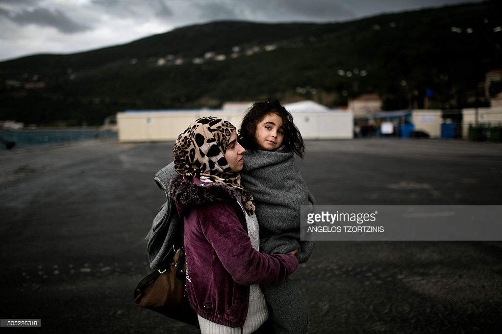 woman-from-syria-holds-her-baby-as-she-arrives-at-the-registration-picture-id505226318